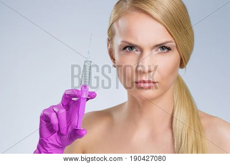 Serious Pretty Woman Holding Syringe In Hand In Glove