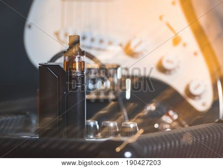 black vaporizer in the smoke among the musical instruments
