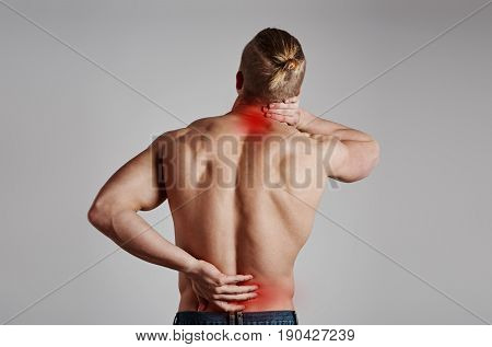 Portrait of athletic male suffering from lumbar vertebrae pain and neck ache. Health care concept.