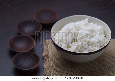 Thai rice in bowl with wooden empty and small bowl on table in dark tone