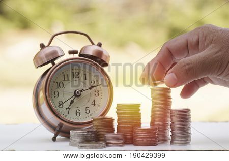 hand put money on pile of coins with clock concept in time to success in bussiness finance bank and account