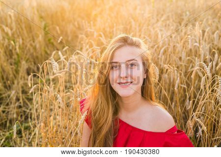 Portrait of a young woman in red dress on a background of golden oats field, summer outdoors.