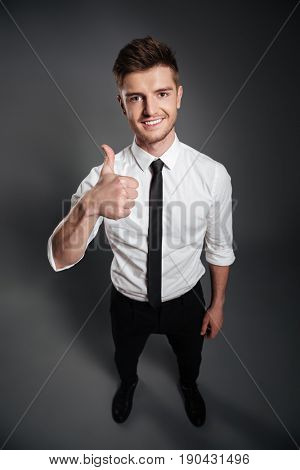 Top view full length portrait of a happy smiling man in white shirt and tie showing thumbs up gesture isolated over grey background