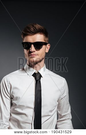 Handsome serious man in sunglasses and formalwear posing and looking away isolated over grey background