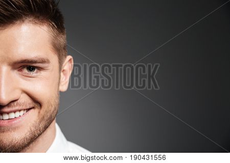 Half face portrait of a handsome smiling young man looking at camera isolated over grey background
