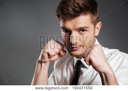 Close up portrait of a confident serious man in shirt and tie boxing isolated over grey background