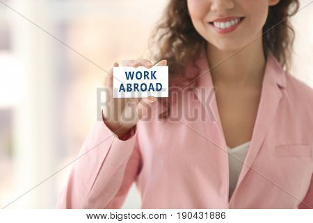 Young woman holding business card with text WORK ABROAD on blurred background. Recruitment concept