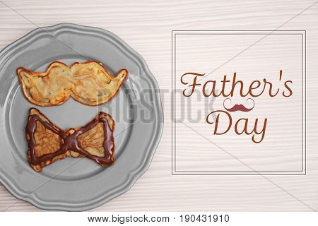 Plate with creative pancakes and text FATHER'S DAY on wooden background