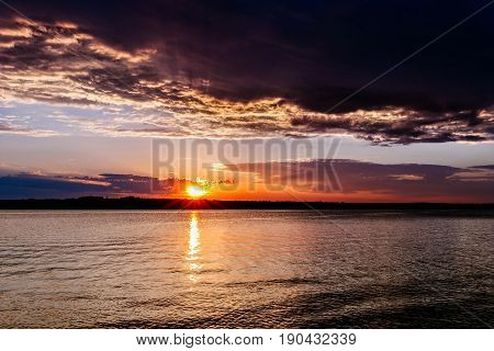 Sunset over a lake with dark clouds in Oklahoma