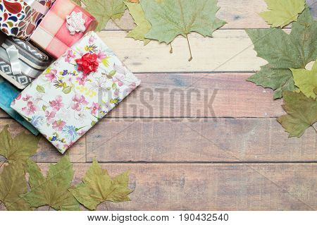 gifts and autumn leaves on wooden table to write a dedication