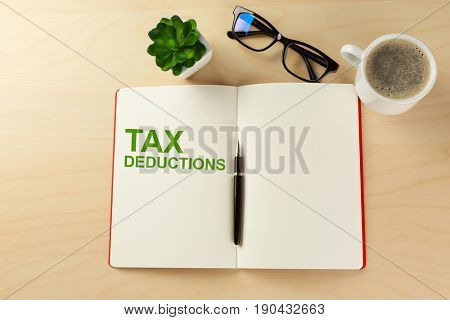 Tax deductions concept. Notebook, glasses and cup of coffee on wooden background