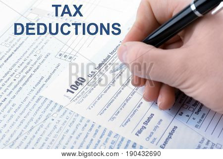 Deductions concept. Woman filling in individual income tax return form, closeup