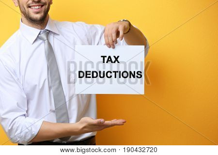 Man holding paper with text TAX DEDUCTIONS on color background