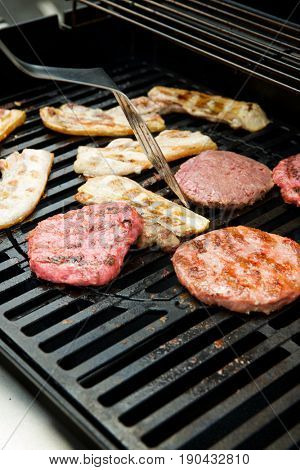 Preparation of a barbecue with sausages, burgers and bacon.