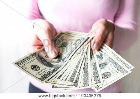 Woman is holding money in her hands. Cash dollar bills.