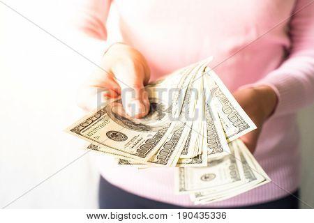 Woman is holding money in her hands. Cash dollar bills. Payment.