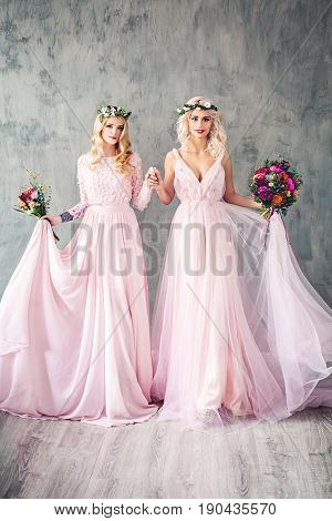 Beautiful Blonde Women in Pink Evening Gown Smiling. Perfect Hairstyle Makeup and Summer Flowers