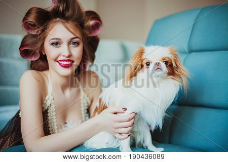 Beautiful young woman wearing curlers posing with japanese chin. Focus is on the dog.