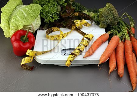 Measuring Tape On White Weight Scale And Vagetables. Dieting Weightloss Slim Down Concept.