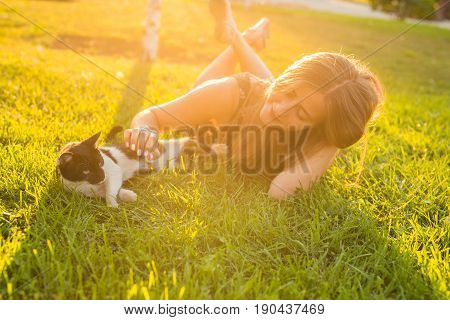young woman with cat outdoors. young happy smiling woman with cat on natural background