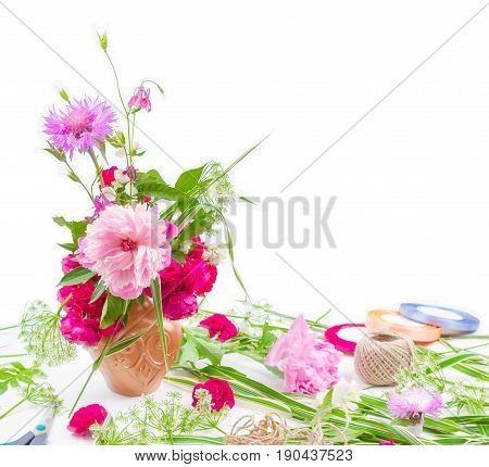 floral design. beautiful bouquet of pink flowers peons cornflowers and red roses on white background with space for text