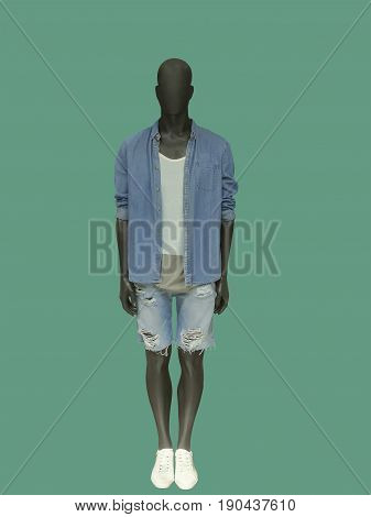 Full-length male mannequin dressed in casual clothes isolated on green background. No brand names or copyright objects.