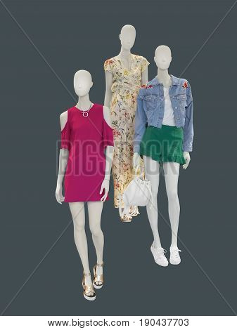 Three female mannequins dressed in fashionable clothes over gray background. No brand names or copyright objects.