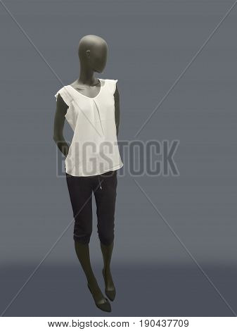 Full-length female mannequin dressed in fashionable clothes. Isolated on gray background. No brand names or copyright objects.