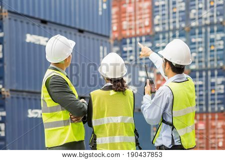 Asian businessmanAsian secretary and Asian Container inspector working in yard with communication device walkie talkie communicate report number checking