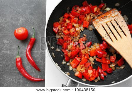 Frying pan with chopped onion and pepper on hot plate