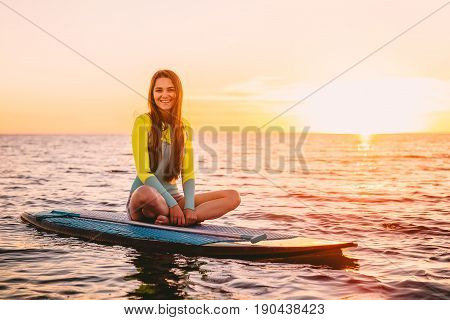 Stand up paddle boarding on sea with warm summer sunset colors. Happy smiling girl on board at sunset