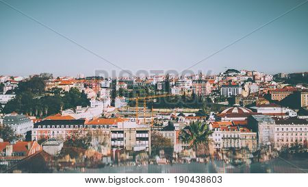 Aerial panoramic shooting from observation point of central Lisbon district on sunny day: multiple ancient houses plants construction cranes clear sky and reflections with aberrations in the bottom