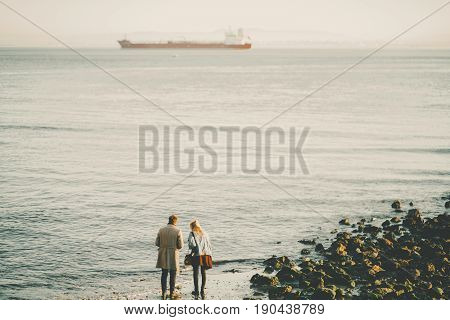 Silhouettes of young couple: man in coat and woman in skirt and jeans jacket standing on sand near water of winter beach in Lisbon with huge cargo barge in distance and hills on misty horizon