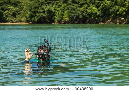 A guy enjoying diving with his head out of the water glasses and snorkle