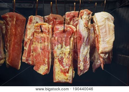 A Variety Of Smoked Meat Products: Sausages, Ham, Bacon, Ribs In The Smokehouse Close Up.