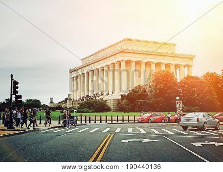 Washington DC; April, 2018- Tourist are walking and driving by car at this busy crosswalk to view the famous presidential Memorial building of the 16th president on a sunny day.