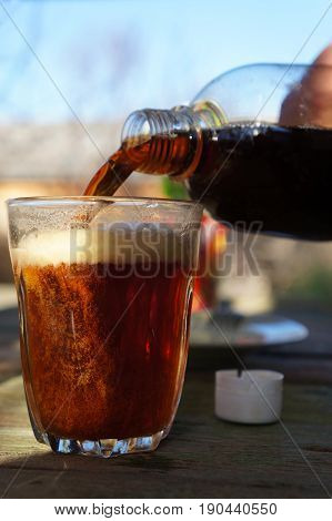 Someone pours a dark beer from a bottle into a glass