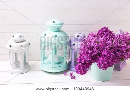 Spring lilac flowers in box and brigh lanterns on white wooden background. Selective focus. Place for text.