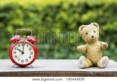 Red alarm clock and toy bear - childbirth concept and greeting card idea