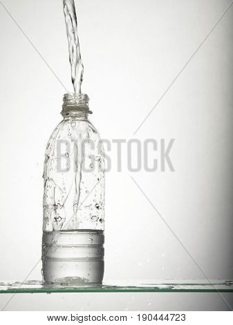 water pouring into mineral water bottle