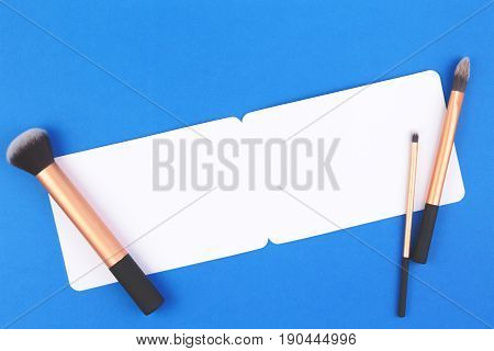 Make up brushes with white blank card on blue background. Top view. Flat lay. Copy space for text