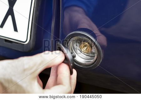 The hand unscrews the plug of LPG gas in the bumper of the car.