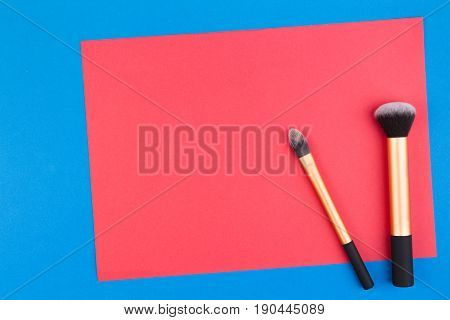 Make up brushes with red blank paper on blue background. Top view. Flat lay. Copy space for text