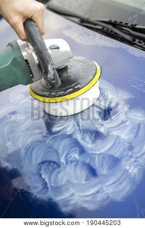 The hands hold an electric polisher and polish the lacquer on the car's bonnet.