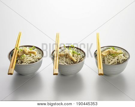 three bowls of noodle with chopsticks on top