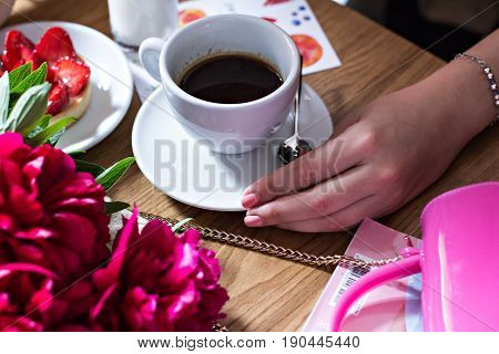 A Cup Of Coffee In A Cafe And A Girl's Hands.