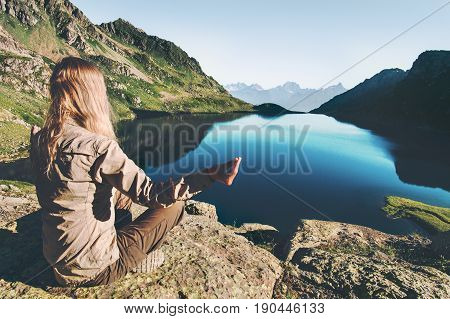 Woman meditating yoga at blue lake in mountains Travel Lifestyle relaxation emotional concept adventure summer vacations outdoor harmony with nature