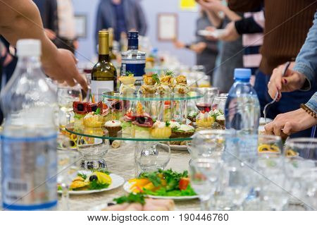 Employees of the company at the Banquet. Table with delicacies, alcohol and snacks. A gala reception. Catering.