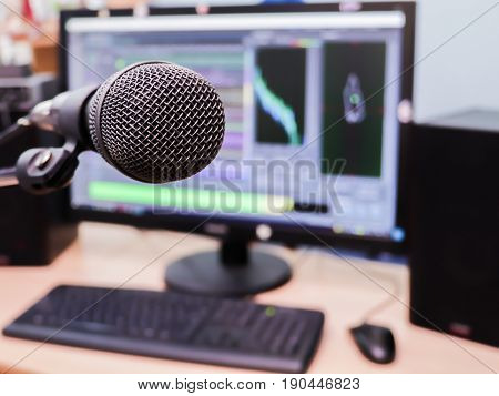 Microphone on the background of the computer monitor. Home recording Studio. Close-up. The focus in the foreground. Blurred background. Software for recording and editing sounds.