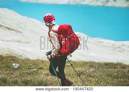 Hiker woman traveling at blue lake mountains with backpack Travel Lifestyle adventure concept summer vacations outdoor active healthy life